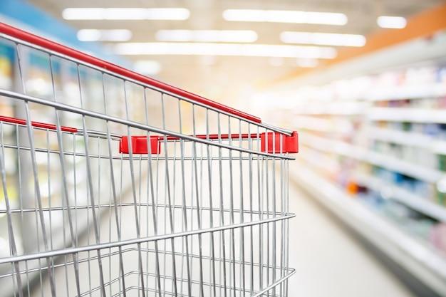 スーパーマーケットの通路は、空の赤いショッピングカートで焦点がぼけた背景をぼかします