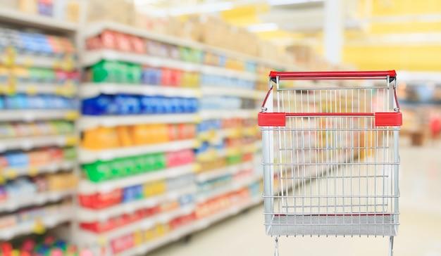 空の赤いショッピングカートでスーパーマーケットの通路のぼやけた背景