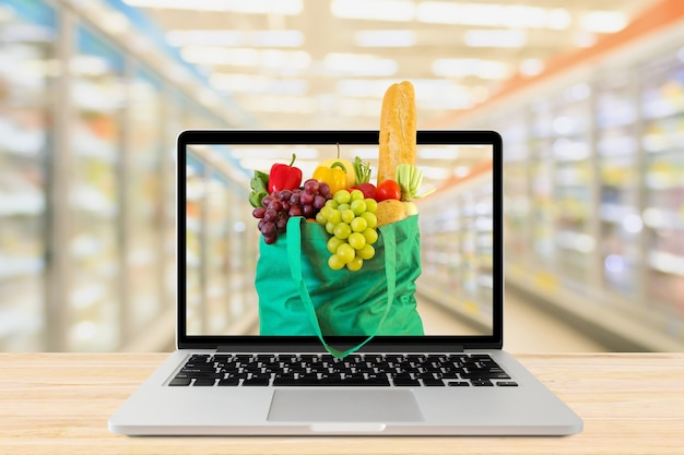 노트북 컴퓨터와 나무 테이블 식료품 온라인 개념에 녹색 쇼핑백 슈퍼마켓 통로 배경을 흐리게