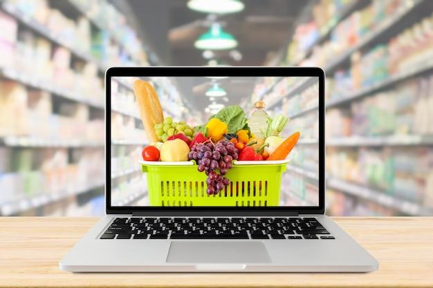 スーパーマーケットの通路には、ラップトップコンピューターと木製のテーブルの食料品の買い物かごの背景がぼやけ