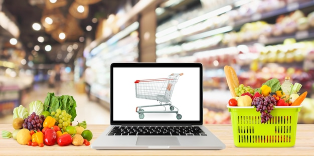Supermarket aisle blurred background with laptop computer and shopping cart