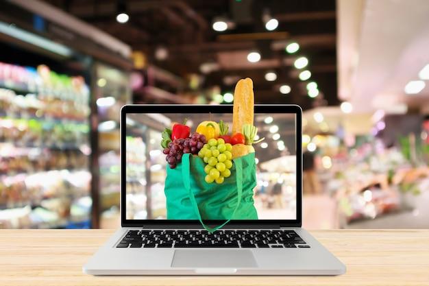 Проход супермаркета с ноутбуком и зеленой сумкой на деревянном столе