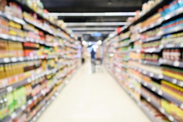 顧客の焦点がぼけたインテリアのスーパーマーケットの通路の製品棚は、ボケ味の明るい背景をぼかします