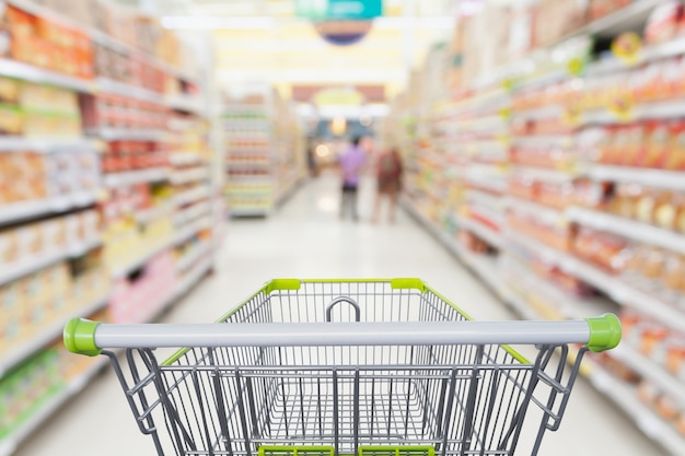 Supermarket aisle with empty shopping cart at grocery store retail business concept