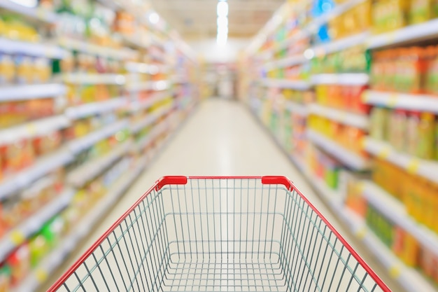 Supermarket aisle with empty shopping cart and product shelves interior defocused