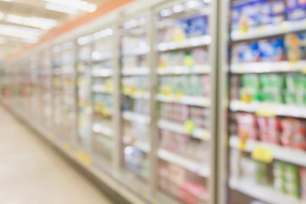 Supermarket aisle with refrigerators blurred background