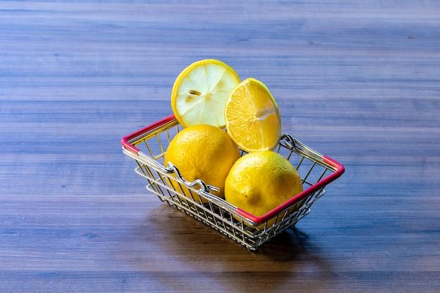 Supermarket basket carrying green leaf and lemon