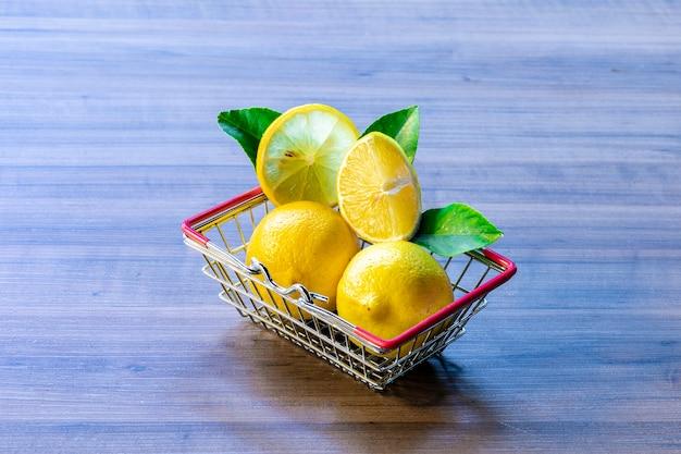 Supermarket basket carrying green leaf and lemon.