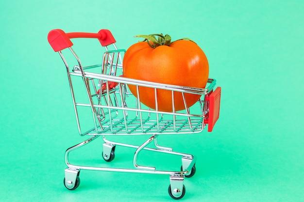 Корзина супермаркета, внутри спелый помидор.