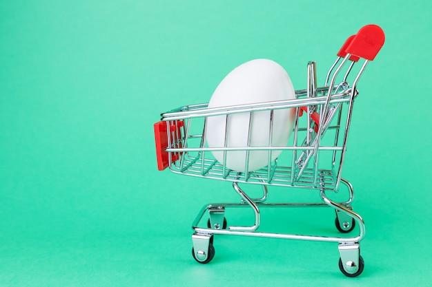 Корзина супермаркета, внутри белое яйцо.