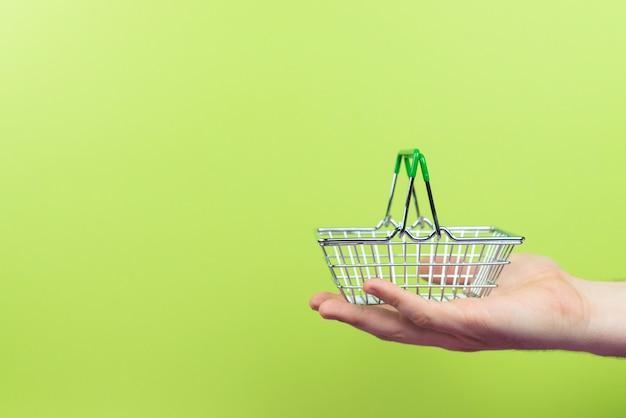 緑のテーブルに手持ちのスーパーマーケットのバスケット