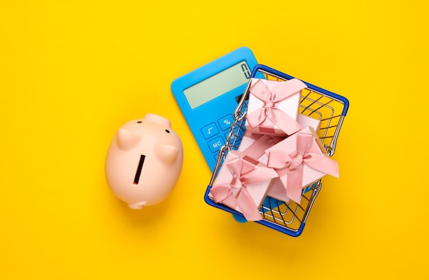 黄色のギフトボックス、貯金箱、電卓が付いたスーパーマーケットのバスケット。