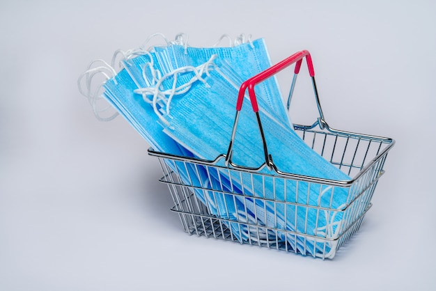 Supermarket basket with protective medical mask and a bottle of alcohol hand gel sanitizer. coronavirus shopping concept on light grey background