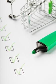 체크리스트 시트에 표시된 슈퍼마켓 카트 및 녹색 마커. 쇼핑 체크리스트 완료 작업 개념.