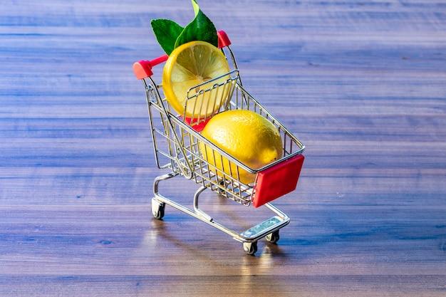Supermarket cart carrying green leaf and lemon