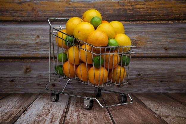木製の背景に柑橘系の果物でいっぱいのスーパーマーケットのカート