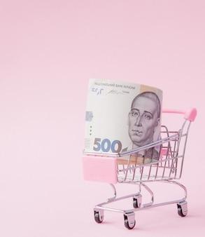 분홍색 배경에 uah 지폐의 전체 슈퍼마켓 카트