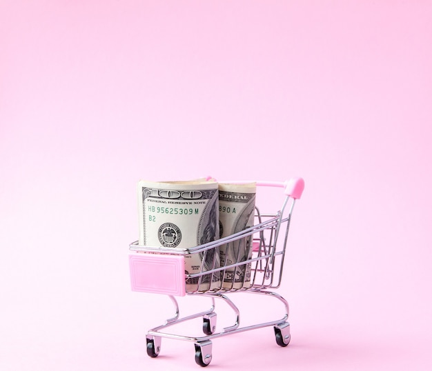 Supermarket cart full of us dollar banknotes on a pink