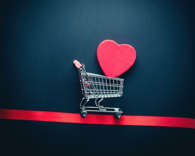 Supermarket cart with heart shape box inside and red ribbon