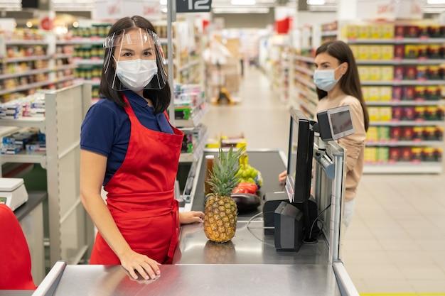 Supermarket cashier and customer following personal protection rules during coronavirus quarantine days, wearing masks