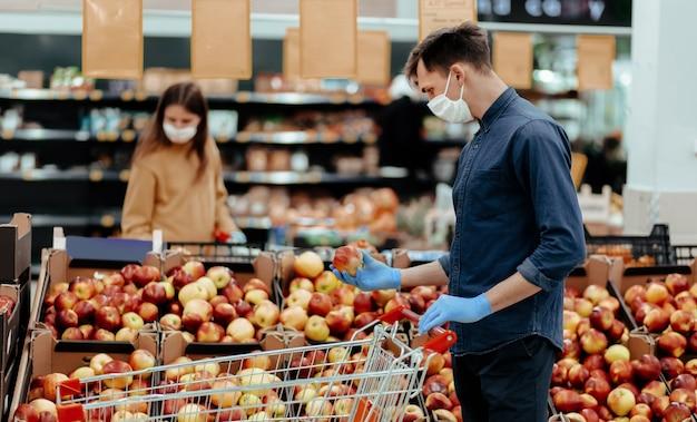 Клиенты супермаркета, стоящие возле прилавка с яблоками