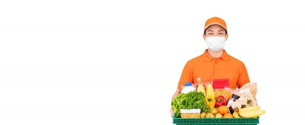 Работник доставляющий покупки на дом супермаркета нося медицинскую маску пока держащ корзину еды и бакалеи изолированный