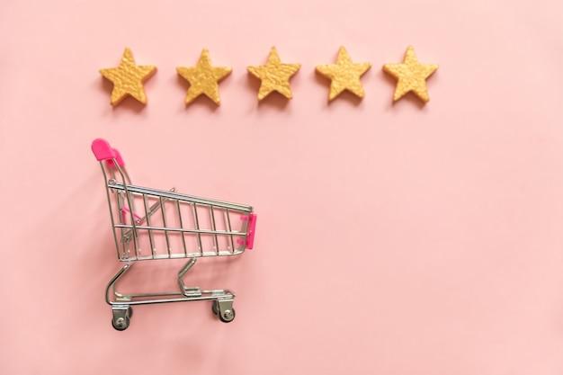 ピンクのパステルカラーの背景に分離されたスーパーマーケットの食料品のプッシュカートの金の星の評価
