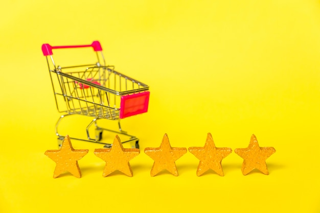 Supermarket grocery push cart for shopping and gold stars rating isolated on yellow background