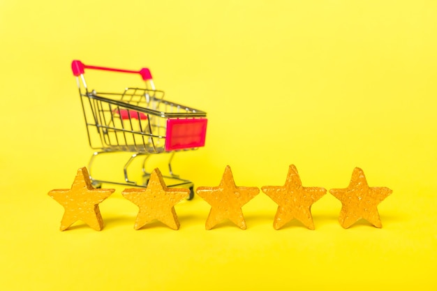 Supermarket grocery push cart for shopping gold stars rating isolated on yellow background