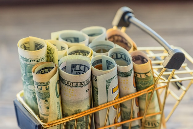 Supermarket grocery pushcart for shopping with bundle of dollars money banknote cash