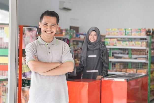 Supermarket owner smiling