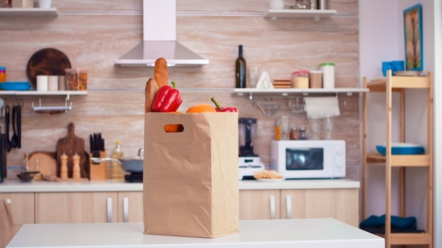 Бумажный пакет супермаркета на кухне со свежими овощами на столешнице. органический образ жизни, здоровая молодежь, покупка в супермаркете, сумка для покупок из свежих овощей