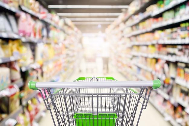空のショッピングカートの焦点がぼけたインテリアのスーパーマーケットの棚の通路は、ボケ味の明るい背景をぼかします