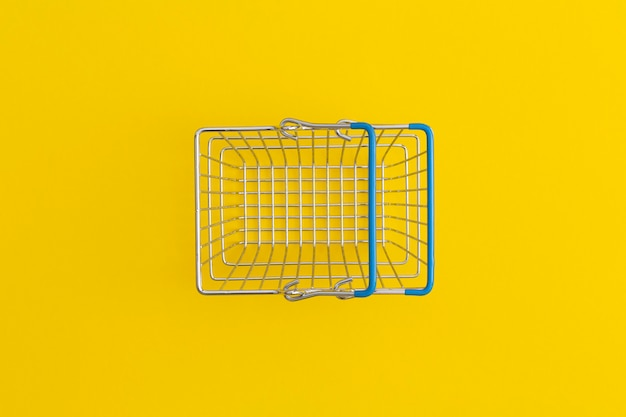 Supermarket shopping basket on yellow background. top view. flat lay