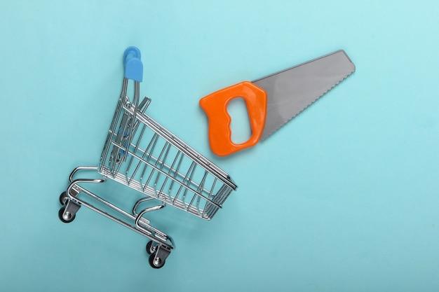 青い背景におもちゃのこぎりでスーパーマーケットのショッピングトロリー。上面図