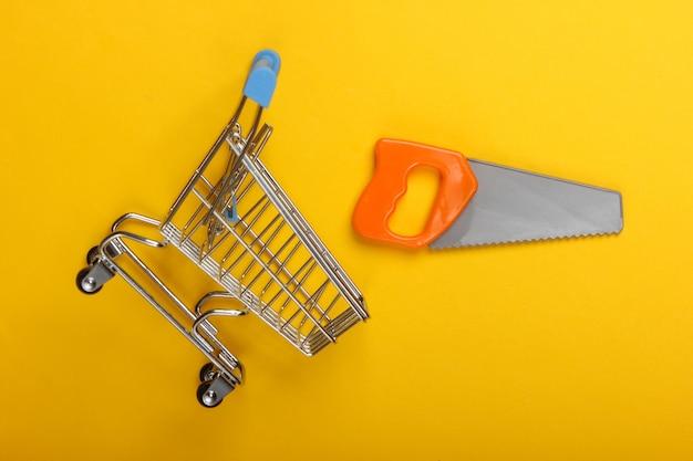 黄色の背景におもちゃのこぎりでスーパーマーケットのショッピングトロリー。上面図