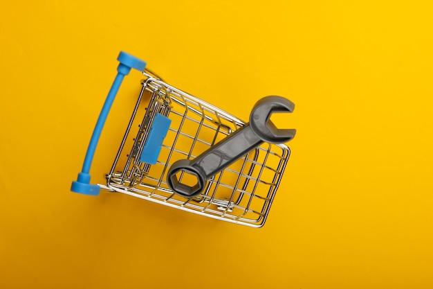 黄色の背景におもちゃのレンチが付いているスーパーマーケットのショッピングトロリー。上面図