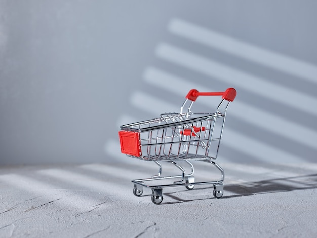 Supermarket trolley on gray background