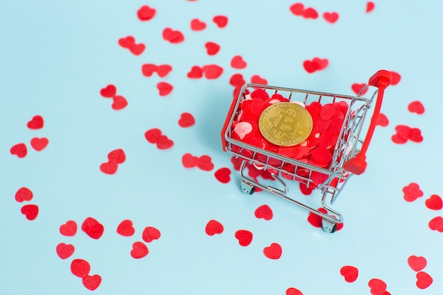 Supermarket trolley is full of red hearts and one golden bitcoin