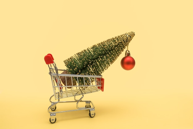 Supermarket trolley with a christmas tree in a basket decorated with a red ball.
