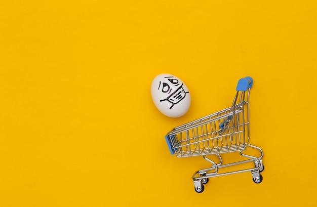 노란색 배경에 의료 마스크에 계란 얼굴이 있는 슈퍼마켓 트롤리. 코로나 19 감염병 세계적 유행. 평면도