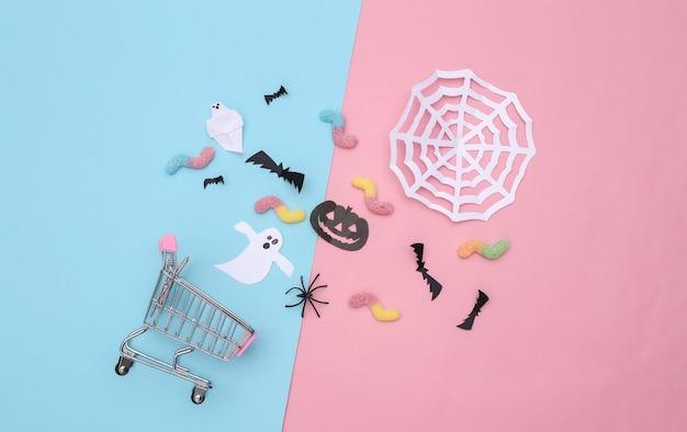 수제 할로윈 종이 장식이 있는 슈퍼마켓 트롤리, 분홍색 파란색 파스텔 배경에 거미 벌레. 평면도