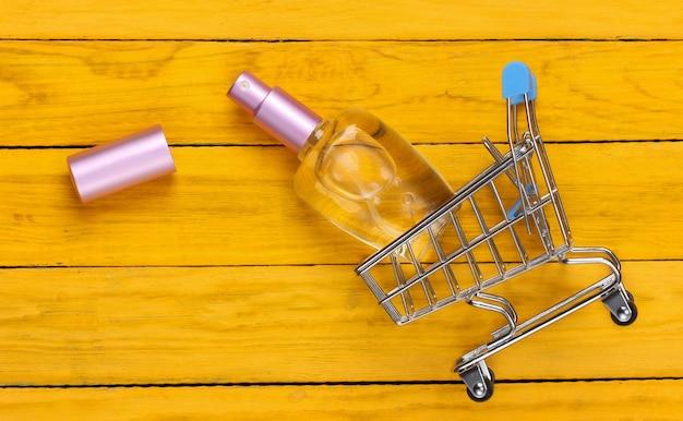 Тележка супермаркета с флаконом духов на желтом деревянном