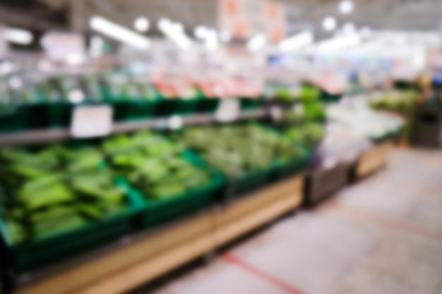 野菜の棚のあるスーパーマーケット焦点の合っていないぼやけた背景