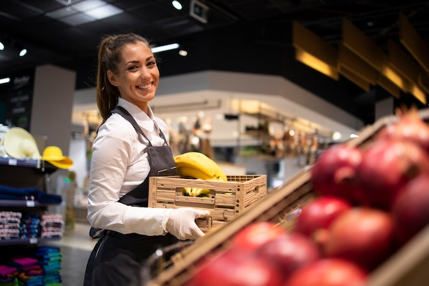 Supermarket worker supplying fruit department with food