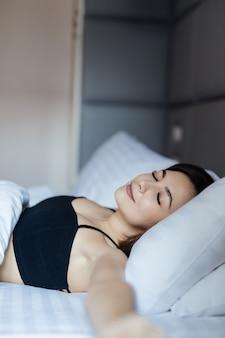 침대에 누워 그녀의 팔을 스트레칭 supersexy 젊은 여자