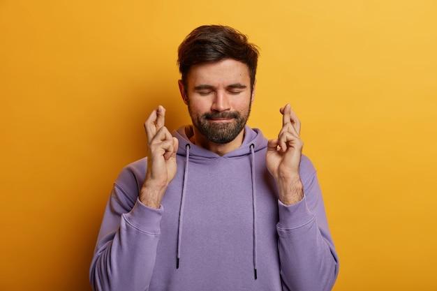 Суеверный бородатый молодой человек скрещивает пальцы на удачу, надежды сбываются, закрывает глаза и сжимает губы, имеет большое желание или мечту, носит фиолетовый свитер, изолированный на желтой стене