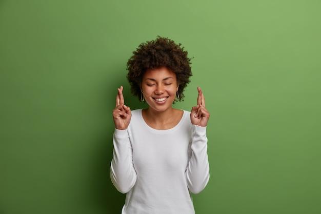 アフロの髪型を持つ迷信的な希望に満ちた女性は、広く笑顔で、夢を実現するために指を交差させ、願いを叶え、より良い生活を信じ、白いジャンパーを着て、緑の壁に隔離されています
