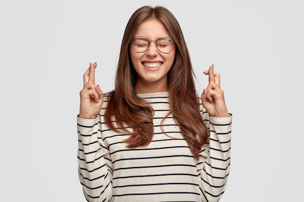 Суеверная позитивная женщина держит пальцы скрещенными, умоляет бога о помощи, желает удачи, одета в полосатую одежду, модели у белой стены, хочет все получить. люди, концепция удачи