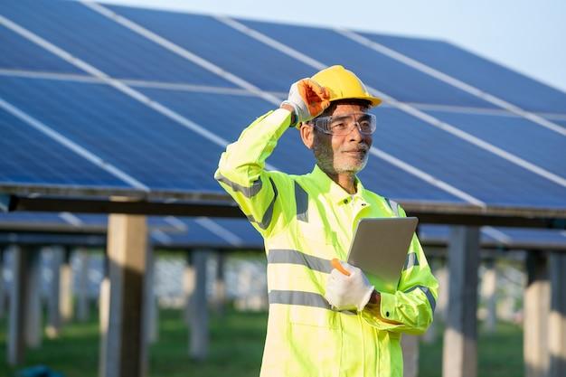 태양 전지판 앞에 서있는 안전 조끼와 안전 헬멧을 착용 한 감독 엔지니어 남성.